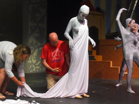 Nicole DiOrio, 16, holds position on stage as costume assistant Jon Bayne uses scissors to shape cloth that will become a dress — part of DiOrio's costume that will transform her into the character of a statue.