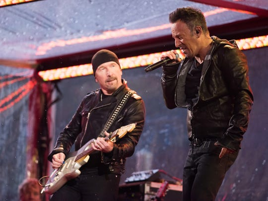 The Edge and Bruce Springsteen perform on Dec. 1, 2014.