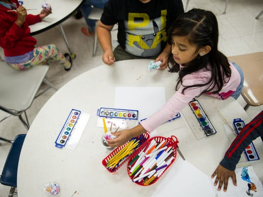 Angie Zelaya, 6, reaches for a paintbrush as she works