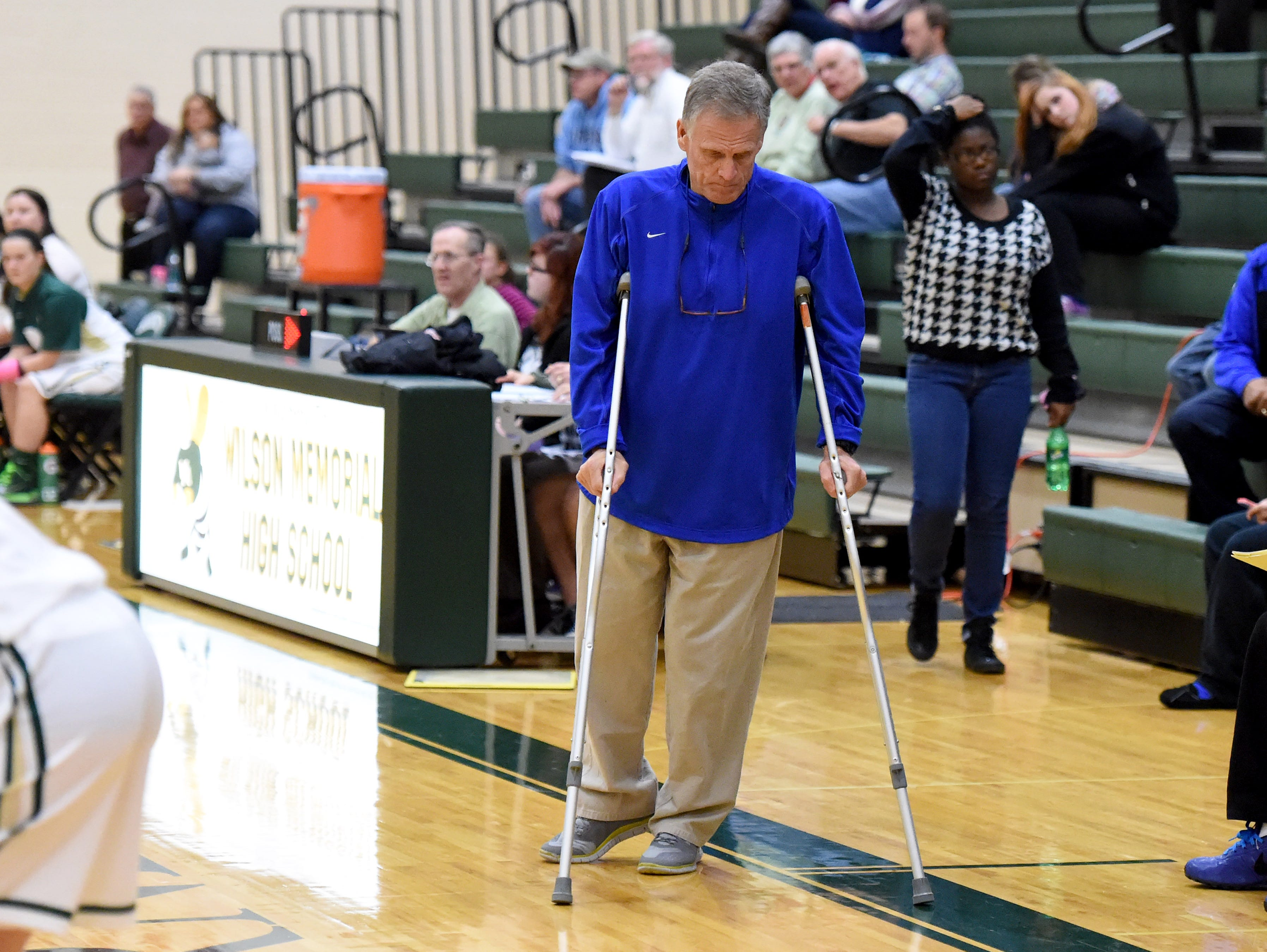 Robert E. Lee girls' basketball coach Dennis Dull uses crutches to get around as he coaches the team against Wilson Memorial on Dec. 15.