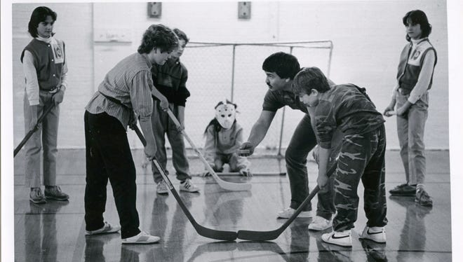 Tim Staley (holding the puck) aligns players for a face-off as players Karen Roush (left front) and Tyler Buzbee, take aim at goalie Sarah Adkins in January of 1986.