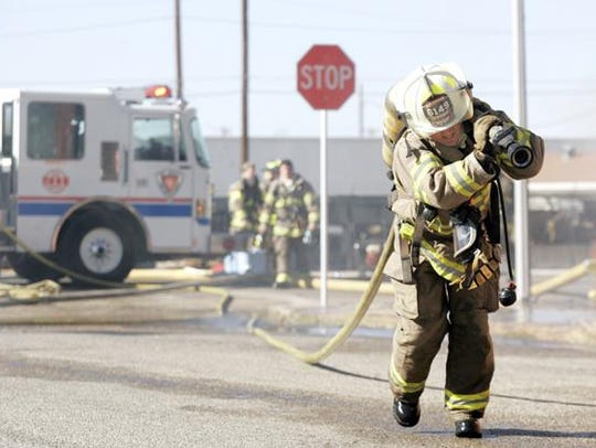 A San Angelo firefighter pulls a fire hose at a scene