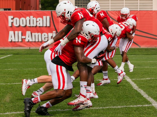 In this Aug. 9, 2016, photo, Nebraska's Tre Bryant, front left, and Nebraska's Tyrin Ferguson , front right, practice rugby-style tackling during NCAA college football team practice in Lincoln, Neb. Nebraska is the latest program to adopt rugby-style tackling where the tackle is made by driving a shoulder into the ball-carrier's near hip, wrapping him up and taking him to the ground. All the while the defender's head is kept to the side of the ball-carrier's body, away from the tackle contact zone. (AP Photo/Nati Harnik)