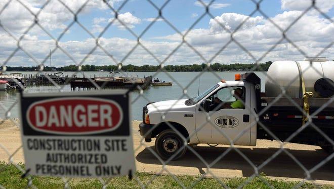 A contractor drives along the dam at Buckeye Lake as a boat docks the Buckeye Lake Yacht Club Tuesday, June 6, 2017, in Buckeye Lake.
