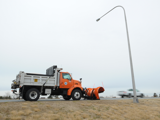 A Delaware Department of Transportation snowplow truck waits on the side of the road for the snow to start Wednesday.
