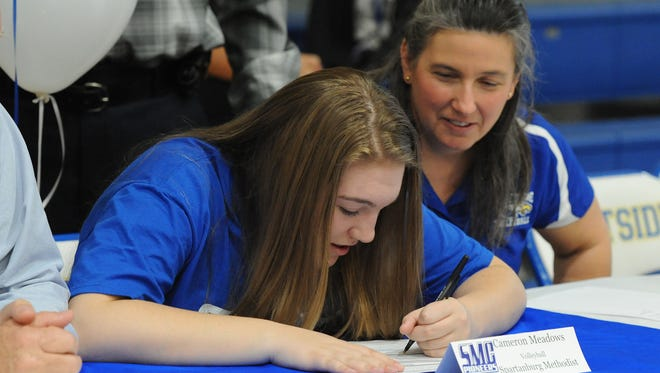 Eastside volleyball coach Susan Meadows looks on as her daughter, Cameron, signs to play volleyball at Spartanburg Methodist College during a pep rally at the school on Wednesday.