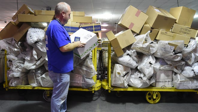 Tim Little, a clerk at the Mountain Home Post Office, checks a bar code on a package Wednesday. Post Master David Fisher expects a 20 percent increase in package volume locally this holiday season.