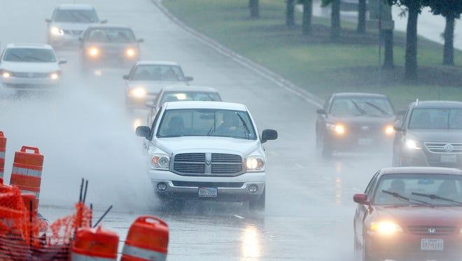 Drivers navigate through a heavy rain shower April 17, 2016, in Richardson, Texas.