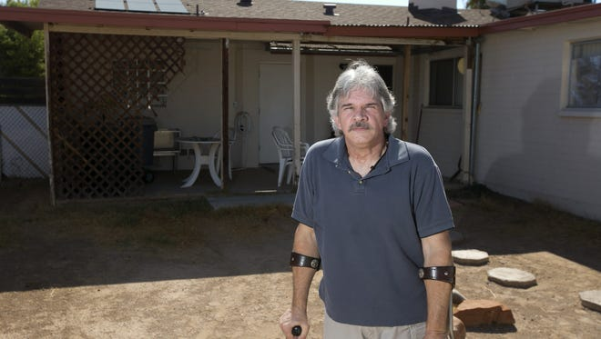 Christopher Renfro says he got duped by telemarketers selling solar equipment and that the company did not honor the contract he signed. He is seen at his home in Phoenix with solar hot water heater panels visible on his roof on Aug. 27, 2015.