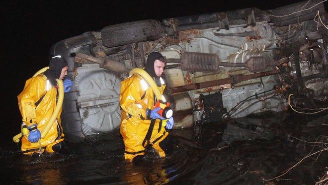 Putnam Lake firefighters look over a car that went into the water Friday night. A woman got out safely.