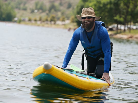 Rustin Hughes steadies himself on a stand up paddle board during Adaptive Watersports Day at Horsetooth Reservoir on Tuesday, June 29, 2016. The annual event, hosted by the City of Fort Collins Recreation Department's Adaptive Recreation Opportunities, provides an opportunity for people with physical disabilities and disabled veterans to go experience the water with the support of adaptive equipment and knowledgeable staff.