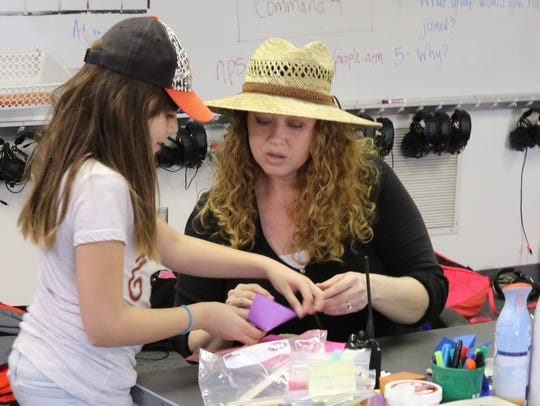 Instructor Tricia LeSuer helps a student with an origami
