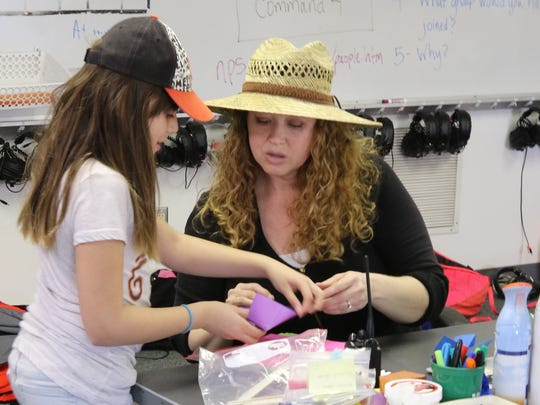 Instructor Tricia LeSuer helps a student with an origami project during an after-school STEM program on Thursday at Mesa Verde Elementary School.