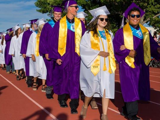 Graduating seniors enter the high school football field.