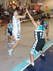 Academy of Our Lady of Guam senior Kiersten Pangelinan throws a no-look pass to freshman Mia San Nicolas during the third quarter of the Cougars' Independent Interscholastic Athletic Association of Guam Girls' Basketball League home game against the Southern High Dolphins on Friday, Nov. 27.