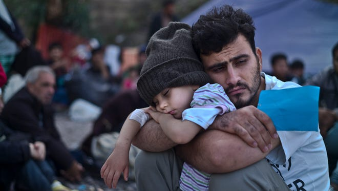 A Syrian refugee child sleeps in his father's arms on Oct. 4 while waiting at a resting point to board a bus, after arriving on a dinghy from the Turkish coast to the northeastern Greek island of Lesbos.