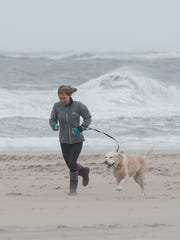 A women runs into strong winds on the beach in Ocean