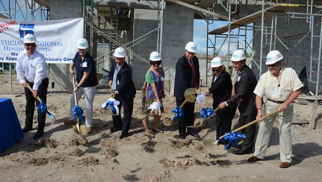 Dignitaries scoop up ceremonial shovelsful of dirt. Physicians Regional held a groundbreaking ceremony Wednesday for their new East Trail clinic, already well underway and scheduled to open early in 2017.