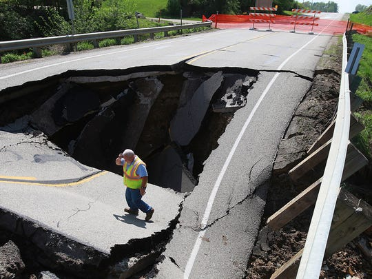 Raydar Milton, a technician with the Osage Municipal Utilities, observes the damage to a portion of Highway 9 west of Osage on May 20, 2013 after a flash flood washed part of a culvert away during a band of intense storms the previous day.