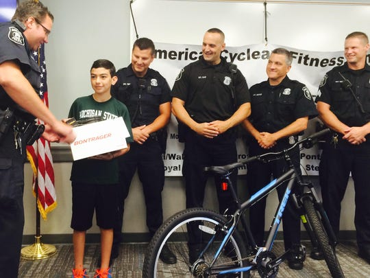 Officer Brian Harbaugh hands over a new bike helmet to Erik Saperstein, donated by American Cycle and Fitness.