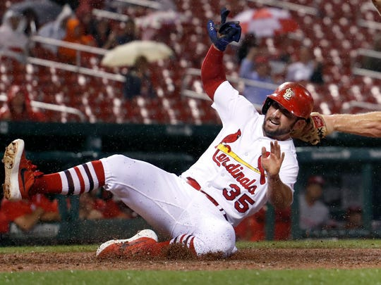 St. Louis Cardinals' Greg Garcia (35) scores ahead of the tag from Cincinnati Reds catcher Stuart Turner during the seventh inning of a baseball game Tuesday, Sept. 12, 2017, in St. Louis.