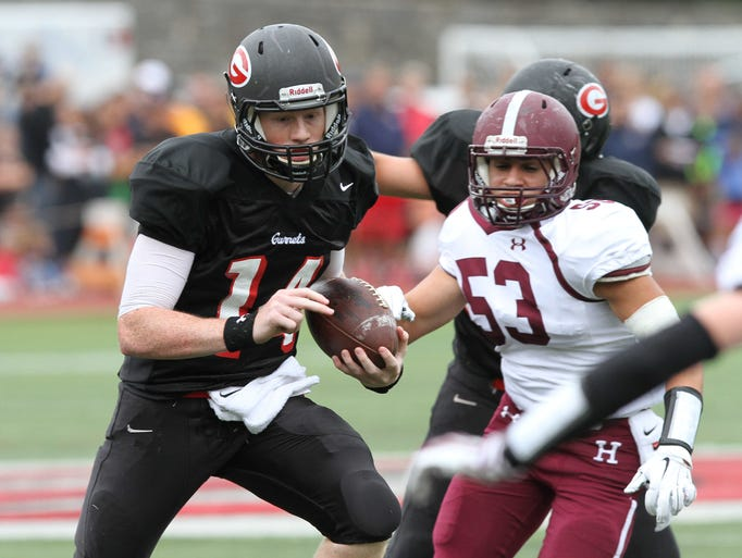 Rye quarterback Andrew Livingston (14) finds some running room in the Harrison defense during the annual Rye-Harrison game at Rye High School Sept. 13, 2014. Rye won the game 24-13.