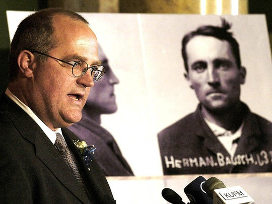 Drew Briner, grandson of Hermann Bausch, pictured in background, who was one of the 78 men and women convicted of sedition in World War I reads from Bauschs' journals, during a pardons ceremony in Helena, Mt., on May 3, 2006. At the end of the ceremony Montana Gov. Brian Schweitzer signed individual pardons for the family members who were present.