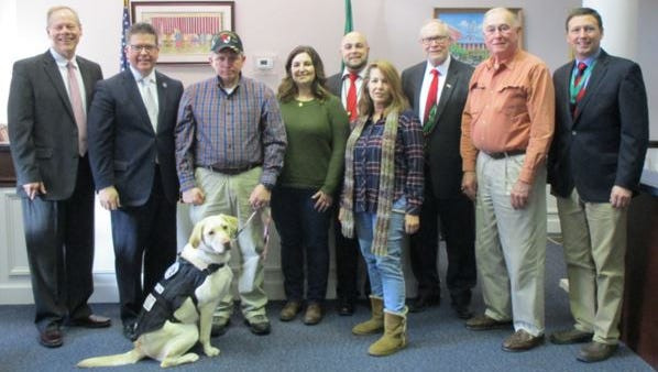 The third partnership in Save-A-Pet Save-A-Pet (from left to right): Commissioner Robert G. Ziobrowski, Chairman David S. Keller, veteran Johnny Gouge and his wife, Jessica, with Skylar, Veteran Affairs Director Justin Slep, trainer Helen Carlson, foster parent Tom Kennedy, and Community Outreach and Events Coordinator John McPaul.