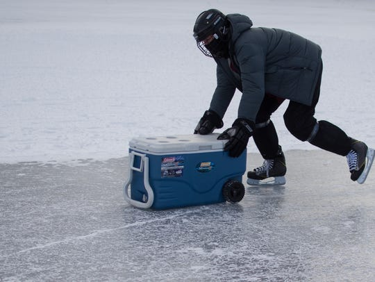 A skater delivers a cooler on Lake Champlain during