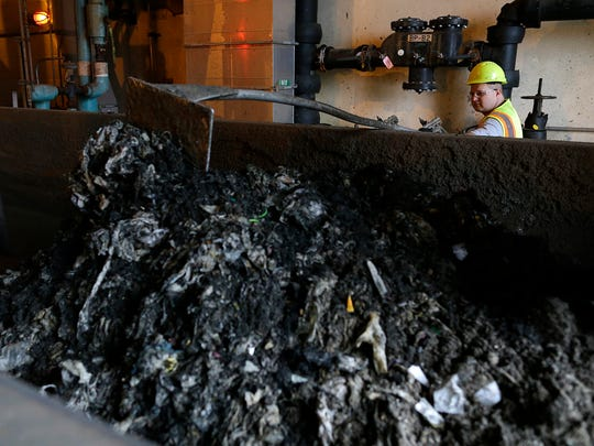 NEW Water's Dave Hoppe monitors a dumpster full of grit, rags, wipes and other various items at NEW Water in Green Bay.