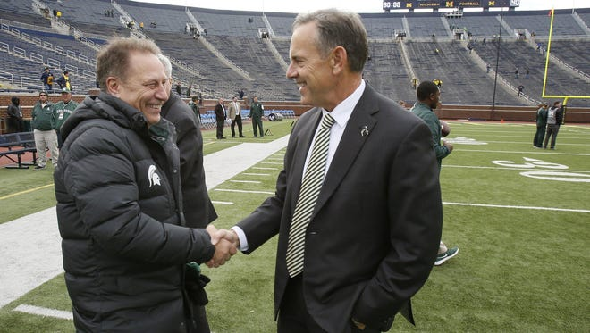 Michigan State basketball coach Tom Izzo greets football coach Mark Dantonio on the field at Michigan Stadium before MSU's football game against Michigan on Oct. 17, 2015 in Ann Arbor.