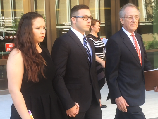 """Philip """"Mitch"""" Brailsford exits Maricopa County Superior Court with his wife and his attorney, Craig Mehrens, on March 15. Brailsford, a Mesa police officer, is charged with second-degree murder following the fatal shooting of Texas resident Daniel Shaver."""