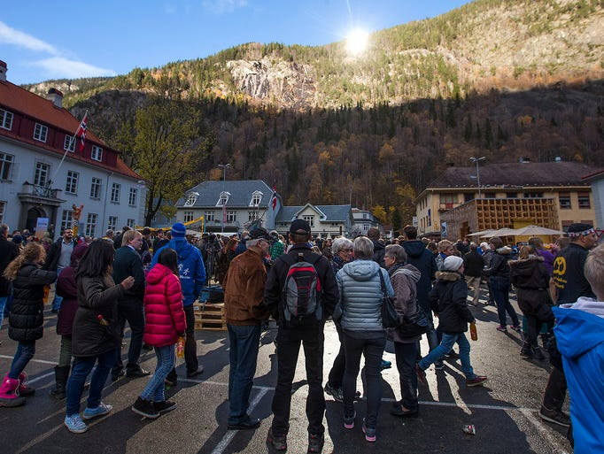 People gather as sunlight reflected off giant mirrors illuminates the town square on Oct. 30 in Rjukan, Norway. Residents of the small town, tucked between steep mountains, normally live in the shade for six months a year.
