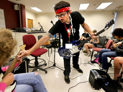 """Instructor Jason Manley, helps Sarah Asbury 16, with a chord during an advanced guitar instrument instruction class at Southern Girls Rock 'N Roll Camp at MTSU, on Thursday July 24, 2014. Hannah Greene """" Rainbow Unicorn"""", 13 plays guitar in the background."""