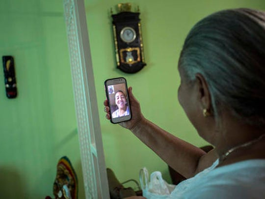 In this Jan. 6, 2017 photo Yolanda Mollinedo looks at her granddaughter Alejandra in Virginia, United States, on her smartphone using a video chat application with the new experimental internet in the living room of her home in Havana, Cuba. The home internet test program selected some 2,000 residents of Old Havana to receive free connections for two months before a planned expansion and the start of billing for the service.
