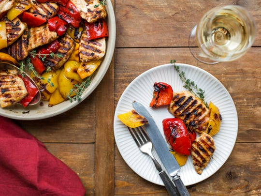 This April 2017 photo shows grilled lemony chicken and peppers in New York. This dish is from a recipe by Katie Workman.