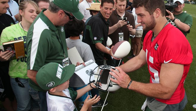 Florham Park, 6/14/12---NY Jets quarterback  Tim Tebow signs autographs for fans after the team's mini-camp and open practice at the Atlantic Health Training Center in Florham Park. Bob Karp/Staff Photographer 2012.