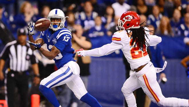 Jan 4, 2014; Indianapolis, IN, USA; Indianapolis Colts wide receiver T.Y. Hilton (13) makes a catch in the end zone for a touchdown while being defended by Kansas City Chiefs cornerback Dunta Robinson (21) during the first quarter of the 2013 AFC wild card playoff football game at Lucas Oil Stadium. Mandatory Credit: Andrew Weber-USA TODAY Sports