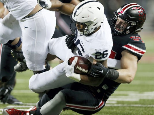 Ohio State defensive lineman Joey Bosa (97) brings down Penn State running back Saquon Barkley (26) during the second quarter in Columbus, Ohio, on Saturday. Barkley ran for 194 yards in the Nittany Lions' 38-10 loss.