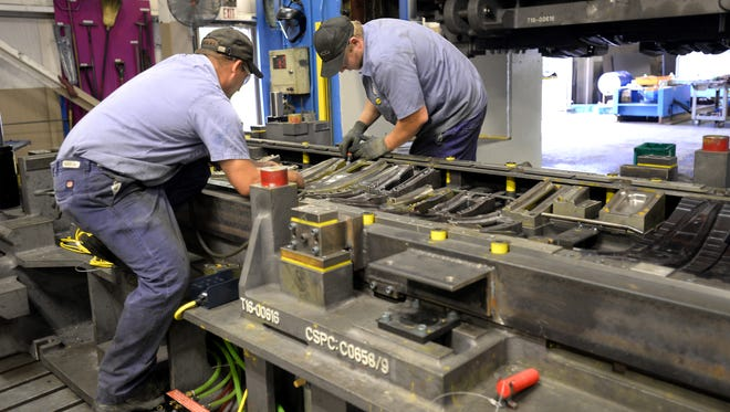 Jim Thompson, left, and Tim Heniser work on a die tryout near the press at Cameron Tool Corp. in Lansing.