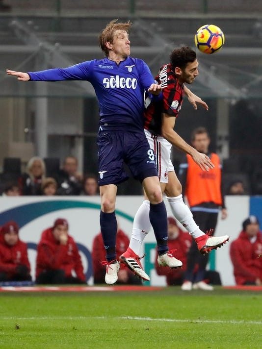 Lazio's Dusan Basta, left, and AC Milan's Hakan Calhanoglu jump for the ball during the Italian Cup, first-leg semifinal soccer match between AC Milan and Lazio, at the Milan San Siro stadium, Italy, Wednesday, Jan. 31, 2018. (AP Photo/Antonio Calanni)
