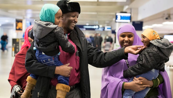 Mohamed lye, carrying his 2-year-old daughter, Nafiso, plays with his 4-year-old daughter, Nimo, carried by family friend Abdinasir Abdulahi, at Minneapolis–Saint Paul International Airport near Bloomington, Minn., after arriving from Amsterdam on  Feb. 5, 2017.
