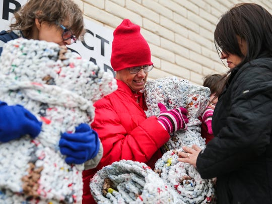 Mosaic client Margaret Webb, Teresa Turner and Project Dignidad director of services Jeannie Solis hold onto five grocery-bag mats made for homeless people Thursday, Dec. 7, 2017, at Project Dignidad.