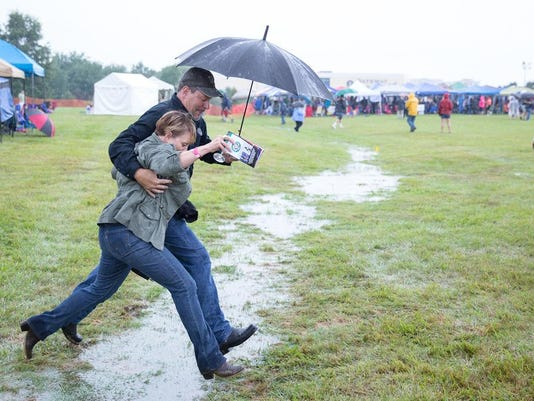 Visitors to the Gettysburg Wine and Music Festival jump across a large puddle during heavy rain on Sept. 12, 2015.