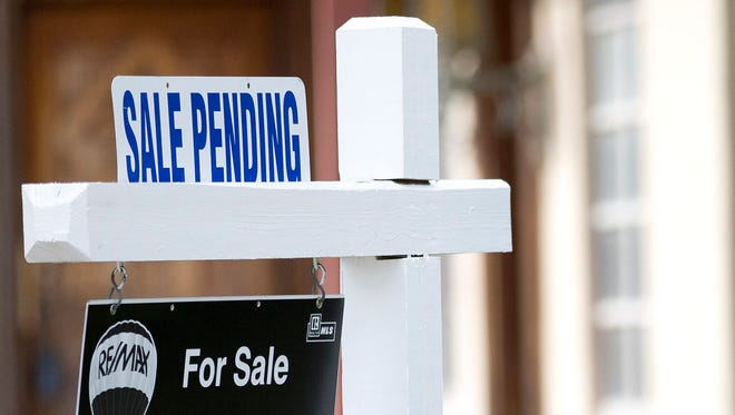 """A """"sale pending"""" sits atop a realty sign outside a home for sale in Surfside, Fla."""
