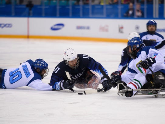 Tyler Carron, middle, battles for the puck during the