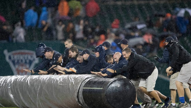 The Tigers grounds crew rolls the tarp onto the field.