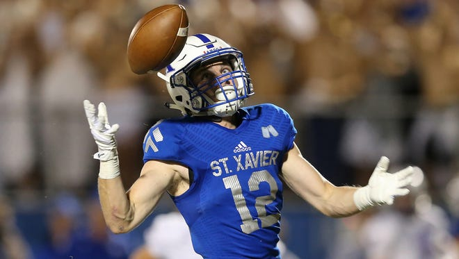 St. Xavier wide receiver Andrew Wittrock (12) eyes a bobbled pass in the fourth quarter during the high school football game between the Elder Panthers and St. Xavier Bombers, Friday, Sept. 29, 2017, at St. Xavier High School in Springfield Township, Ohio.