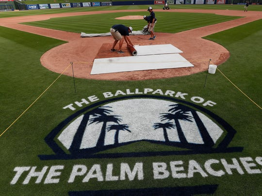 Grounds crew members work to ready the field at the FITTEAM Ballpark of the Palm Beaches before a spring training baseball game between Houston Astros and Washington Nationals.