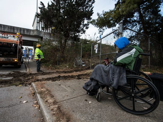 "Byron ""Roc"" Peeler sat on the sidewalk and watched as his belongings were removed from a homeless camp between Jefferson Street and I-65. Dec. 8, 2017."